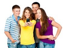 Grupp av ungdomar med telefonen royaltyfri bild