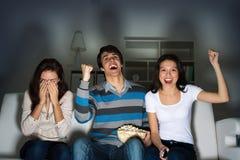 Grupp av ungdomarhållande ögonen på TV på soffan Royaltyfri Bild