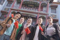 Grupp av ungdomarhållande kinesiska flaggor, stående. Royaltyfri Foto