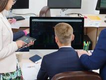 Grupp av ungdomari kontoret som ser datorskärmen arkivbild