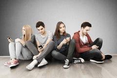 Grupp av ungdomarmed smartphones Arkivfoton