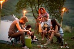 Grupp av ungdomarpå natten i tältplats royaltyfri foto
