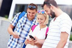 Grupp av ungdomarsom använder smartphones Arkivbilder