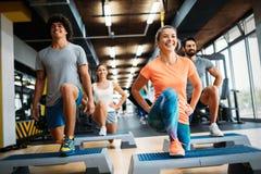 Grupp av ungdomarsom gör övningar i idrottshall royaltyfri foto