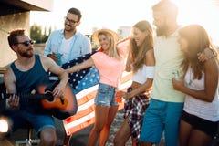 Grupp av ungdomarsom har gyckel på ett sommartidparti, på solnedgången royaltyfria foton