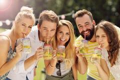 Grupp av ungdomarsom hurrar och har rolig det fria med drinkar Royaltyfri Foto