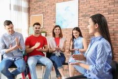 Grupp av ungdomarsom lär teckenspråk med läraren royaltyfria foton
