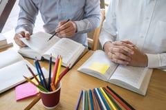 Grupp av ungdomarsom l?r studera ny kurs till kunskap i arkiv under att hj?lpa undervisa v?nutbildning f?r att f?rbereda sig f?r royaltyfri fotografi