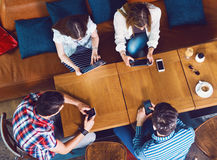Grupp av ungdomarsom sitter på ett kafé, med mobiler och minnestavlor Fotografering för Bildbyråer