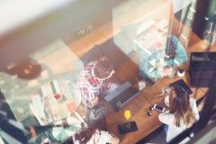Grupp av ungdomarsom sitter på ett kafé, med mobiler och minnestavlor Royaltyfri Bild