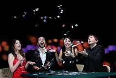 Grupp av ungdomarsom spelar poker på dobblerihuset royaltyfri foto