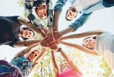 Grupp av ungdomarsom står i en cirkel, utomhus Fotografering för Bildbyråer