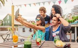 Grupp av ungdomarsom tar en selfie med minnestavlan Royaltyfri Bild