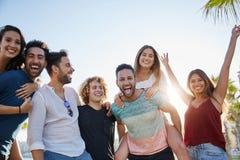 Grupp av ungdomarsom tillsammans utanför skrattar royaltyfria bilder