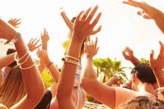 Grupp av ungdomarsom tycker om utomhus- musikfestival royaltyfri bild