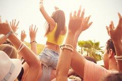 Grupp av ungdomarsom tycker om utomhus- musikfestival royaltyfria foton