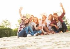 Grupp av ungdomarsom utomhus tar en selfie på stranden royaltyfri foto