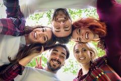 Grupp av ungdomartillsammans utomhus i stads- bakgrund Fotografering för Bildbyråer