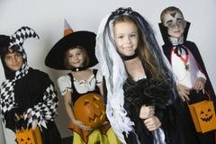 Grupp av ungen i allhelgonaaftondräkter Arkivfoto