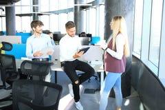 Grupp av ungt affärsfolk som tillsammans arbetar och meddelar i idérikt kontor royaltyfri foto