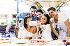 Grupp av ungt härligt folk som sitter i en restaurang och en taki Fotografering för Bildbyråer