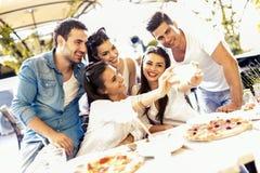 Grupp av ungt härligt folk som sitter i en restaurang och en taki Arkivbild