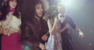Grupp av ungt lyckligt folk som dansar i diskoklubban lager videofilmer