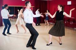 Grupp av ungt lyckligt folk som dansar vridningen arkivbild