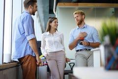 Grupp av ungt modernt folk i smarta tillfälliga kläder som har ett kläckning av ideermöte, medan stå i det idérika kontoret royaltyfria foton