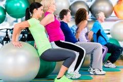 Grupp av ungt och högt folk som övar i idrottshall Royaltyfri Bild