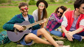 Grupp av ungt stiligt folk på picknicken, medan de spelar gitarren och sjunger stock video