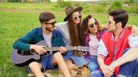 Grupp av ungt stiligt folk på picknicken, medan de spelar gitarren och sjunger Vänner på sommarbegreppet stock video