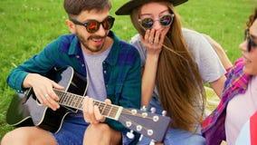 Grupp av ungt stiligt folk på picknicken, medan de spelar gitarren och sjunger Vänner på sommarbegreppet arkivfilmer