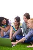 Grupp av ungt studentsammanträde på grönt gräs Arkivbild