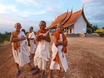 Grupp av unidentified buddistisk novis som beside ler av kyrka royaltyfria bilder