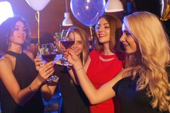 Grupp av ursnygga Caucasian unga flickor i eleganta klänningar som ler dricka vin som rostar fira födelsedag i ett kafé fotografering för bildbyråer