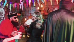 Grupp av vännen som har massor av gyckel som kläs som ont tecken på ett halloween parti i en lokal bar stock video