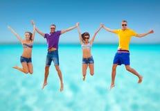 Grupp av vänner eller par som hoppar på stranden Fotografering för Bildbyråer