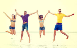 Grupp av vänner eller par som hoppar på stranden Arkivfoto