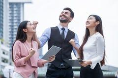 grupp av vänner för ung man som och kvinnaanvänder en minnestavla och utomhus skrattar tre personer av upphetsande affär för team royaltyfri bild