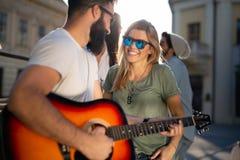 Grupp av vänner för unga kvinnor som har gyckel och spelar gitarren fotografering för bildbyråer