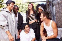 Grupp av vänner i anseende för stads- inställning vid staketet royaltyfri fotografi