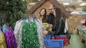 Grupp av vänner i en supermarket som väljer julpynt, glitter och banderoller lager videofilmer