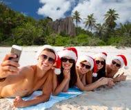 Grupp av vänner i santa hattar med att ta selfie arkivfoto