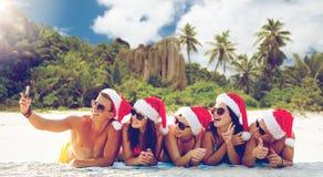 Grupp av vänner i santa hattar med att ta selfie royaltyfria foton