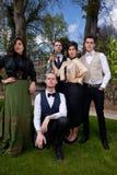 Grupp av vänner i viktorianska kläder, kolonn och royaltyfri fotografi