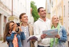 Grupp av vänner med den stadshandboken, översikten och kameran fotografering för bildbyråer