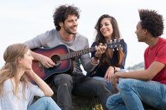 Grupp av vänner med gitarren Fotografering för Bildbyråer
