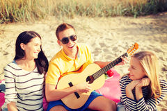 Grupp av vänner med gitarren som har gyckel på stranden Royaltyfri Fotografi