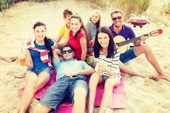 Grupp av vänner med gitarren som har gyckel på stranden Royaltyfri Foto